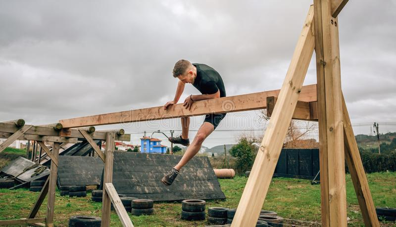 Participant in a obstacle course doing irish table. Male participant in a obstacle course doing irish table obstacle stock photography