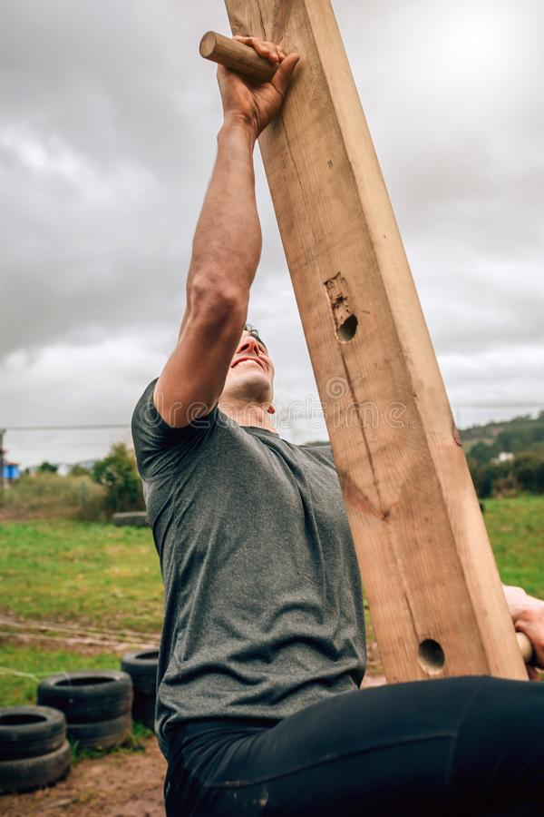Participant in a obstacle course doing pegboard. Male participant in a obstacle course doing pegboard obstacle royalty free stock photos