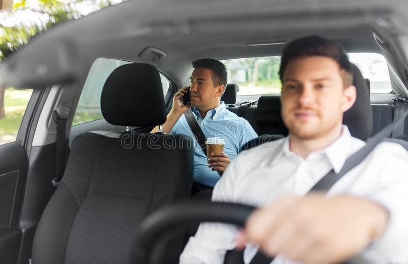 Male passenger with coffee calling on phone in car. Transportation, vehicle and people concept - middle aged male passenger with takeaway coffee cup calling on stock photo