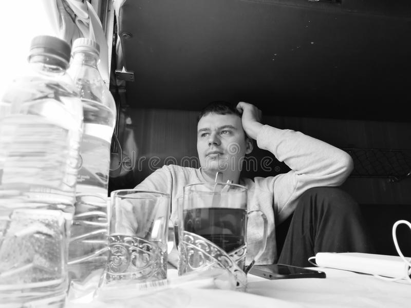 Male passenger is sitting in a compartment of an old train car. stock photo