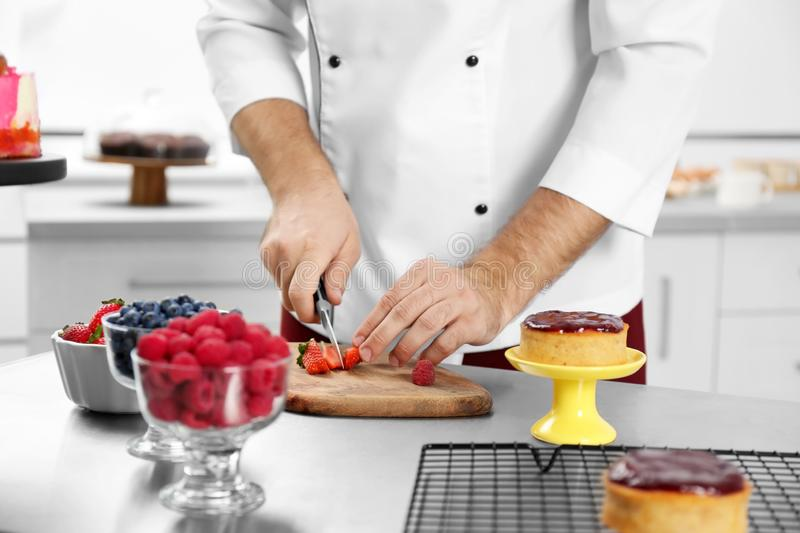 Male pastry chef preparing dessert at table in kitchen stock photography