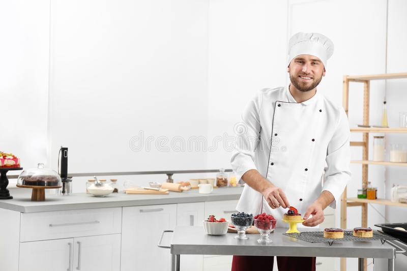 Male pastry chef preparing dessert at table royalty free stock photography