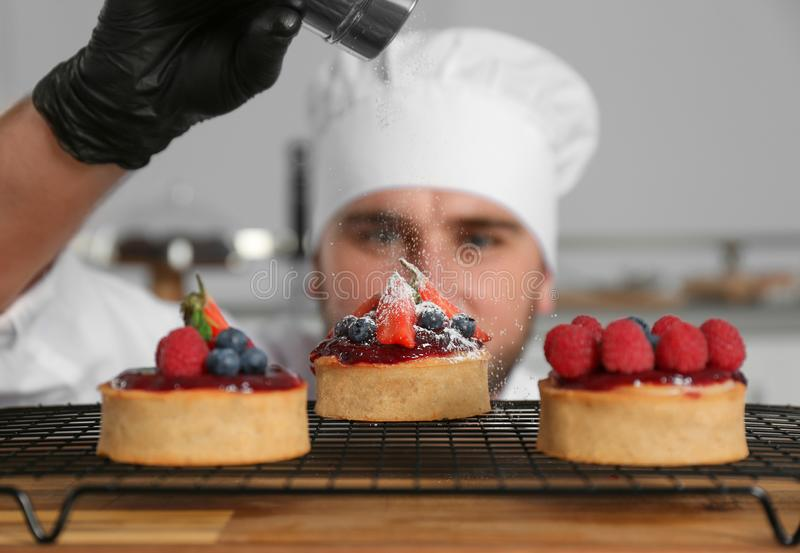 Male pastry chef sprinkling desserts with sugar powder. In kitchen royalty free stock image