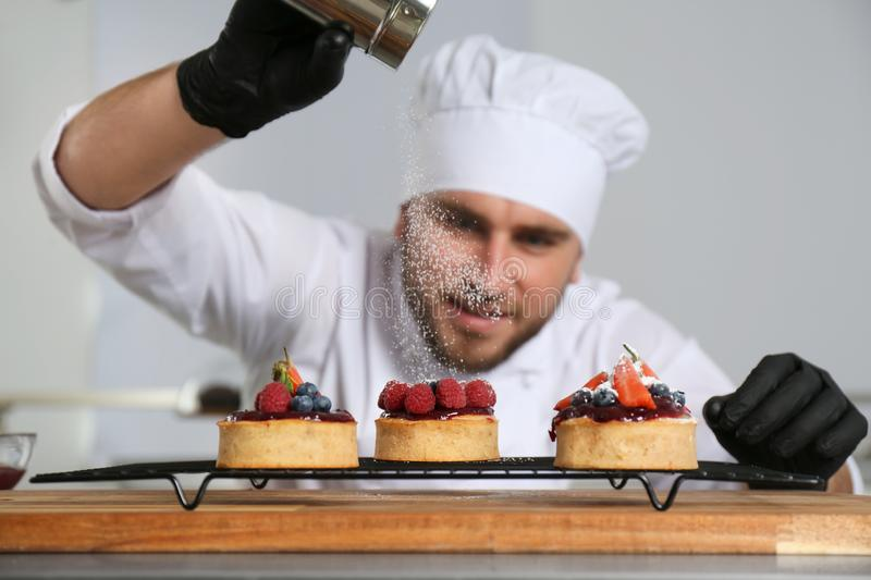 Male pastry chef sprinkling desserts with sugar powder stock photos