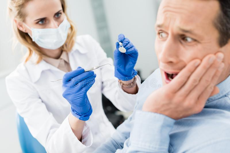 Male patient is afraid of dentist in modern stock photos