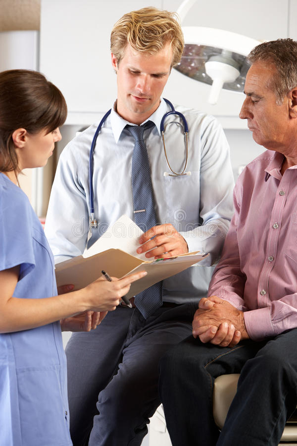 Download Male Patient Being Examined By Doctor And Intern Stock Image - Image: 28851601