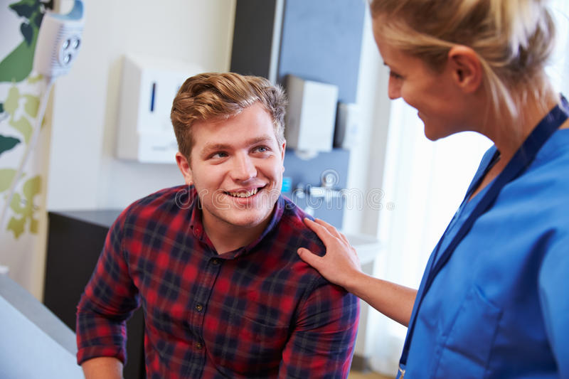 Male Patient Being Reassured By Nurse In Hospital Room stock photos
