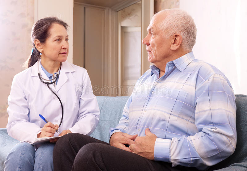 Male patient complaining of pain in side to docto royalty free stock images