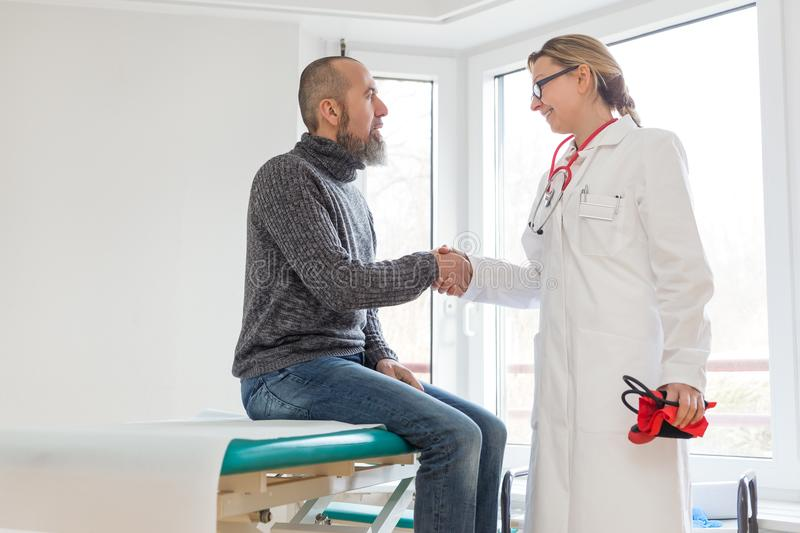 Male patient is consulting a female doctor. In her office or practice stock photos
