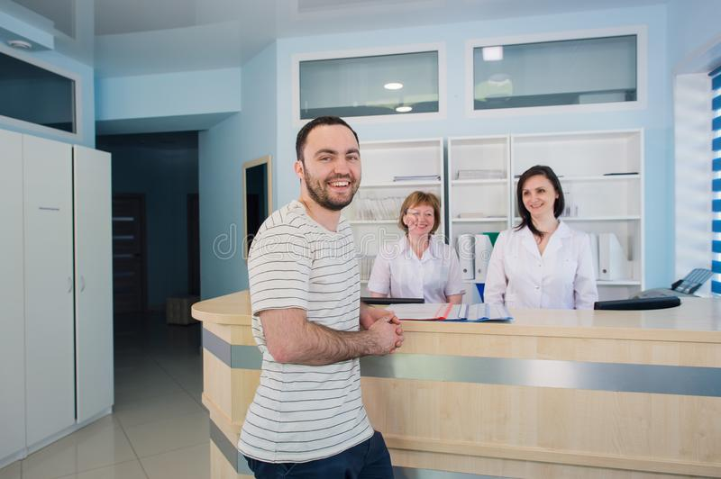 Male patient with doctor and nurse at reception desk in hospital.  royalty free stock image