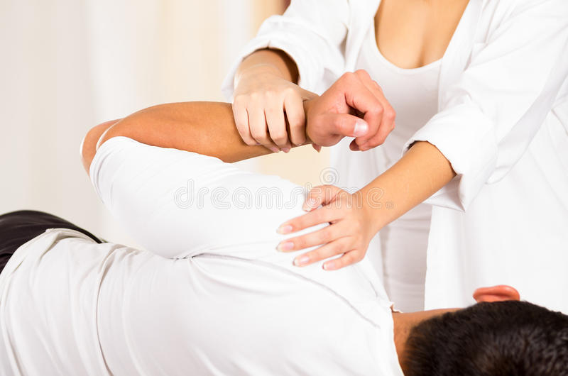 Male patient lying down sideways with female physio therapist performing some stretch excercises stock images