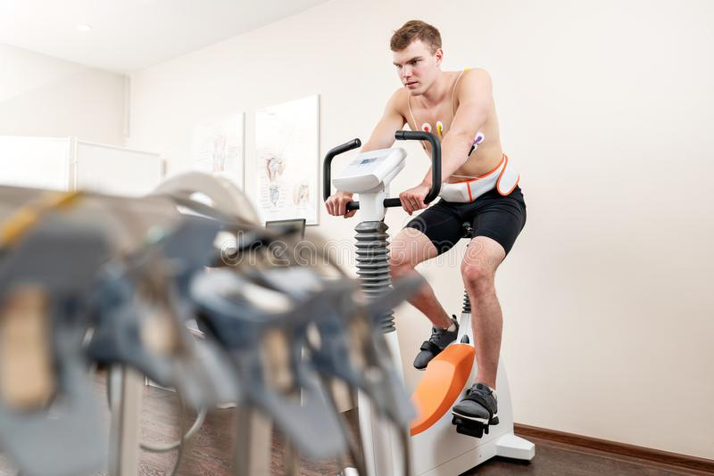 A male patient, pedaling on a bicycle ergometer stress test system for the function of his heart checked. Athlete does a. Cardiac stress test in a medical study stock image