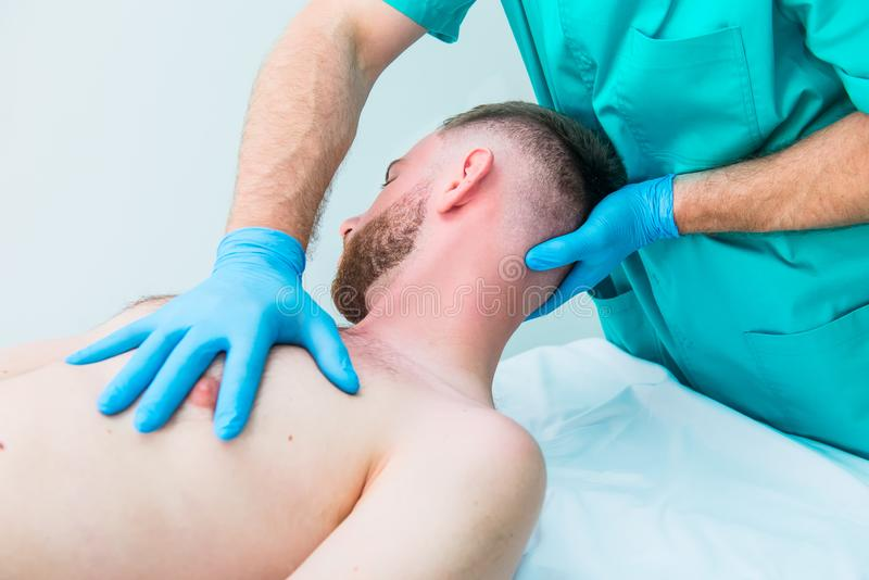 Male patient receiving massage from therapist. A chiropractor stretching his patient`s neck in medical office. Neurological stock images