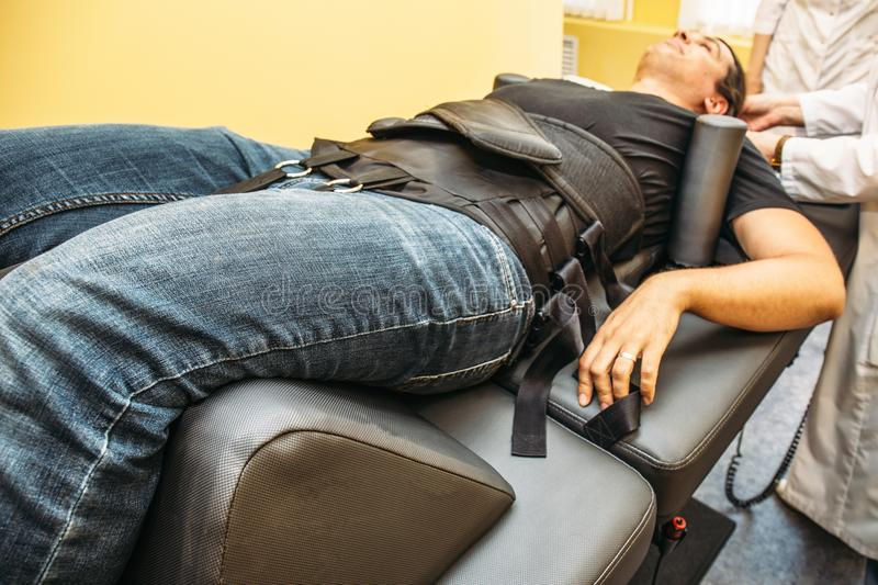 Male patient on treatment of intervertebral discs and spinal hernia, stretching spine on special medical machine tool royalty free stock photography