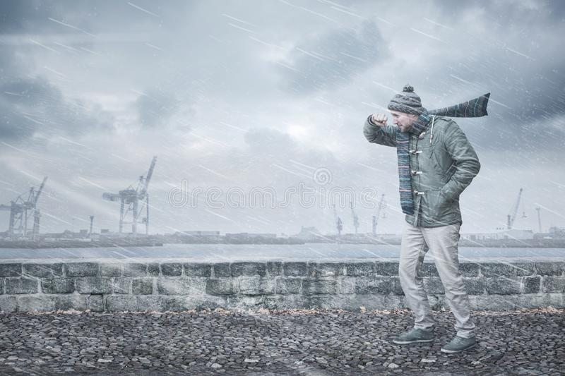 Male pedestrian is facing strong wind and rain. A pedestrian is walking down a footpath on a dockside. He is opposing a strong wind and rain shielding his face royalty free stock image