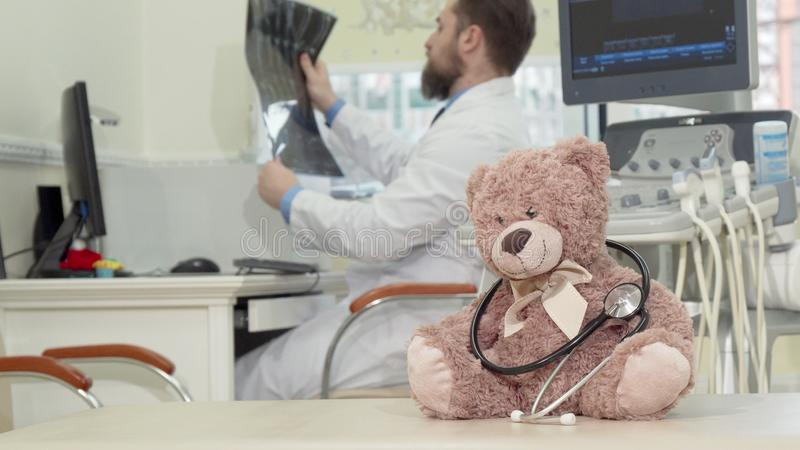Male pediatrician examining mri scan, plush toy teddy bear on the foreground stock image
