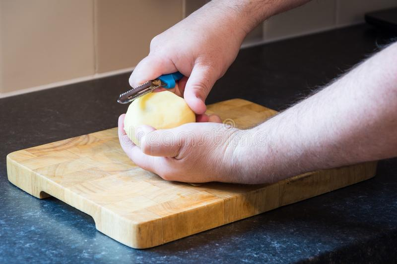 Male peeling potato over a wooden chopping board in kitchen with black work surface. Male prepares food by peeling potato with a blue handle potato peeler over a stock photo