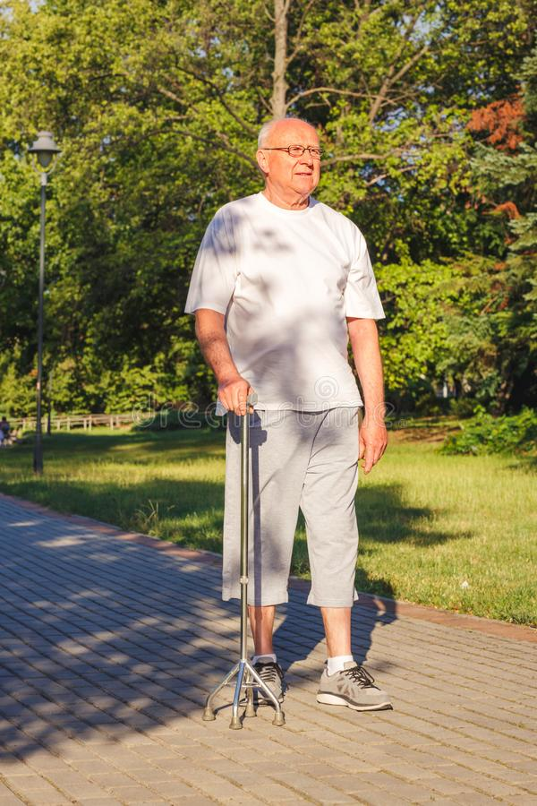 Male pensioner enjoying walk in park with stick royalty free stock photo