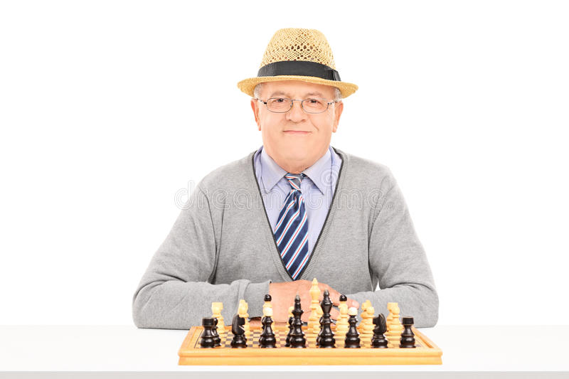 Male pensioner posing behind a chessboard. Isolated on white background stock photography