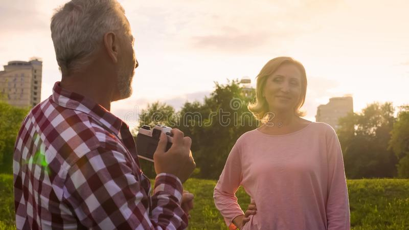 Male pensioner taking picture of attractive senior woman in park, hobby, date royalty free stock image