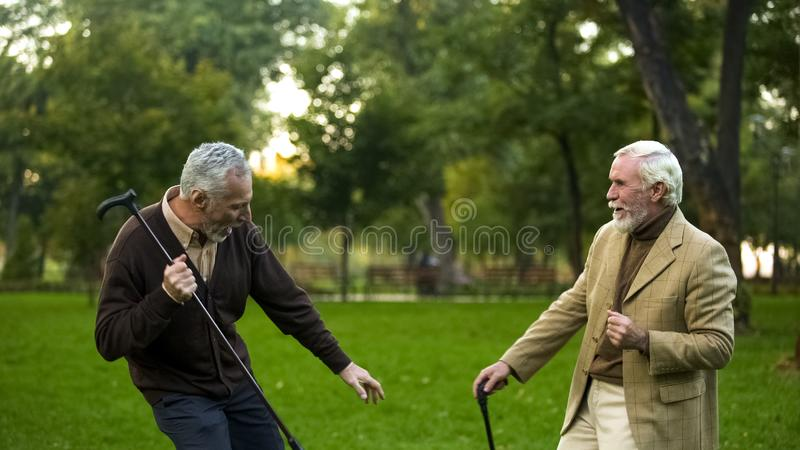 Male pensioners dancing park with walking sticks, friendship humor, having fun stock images