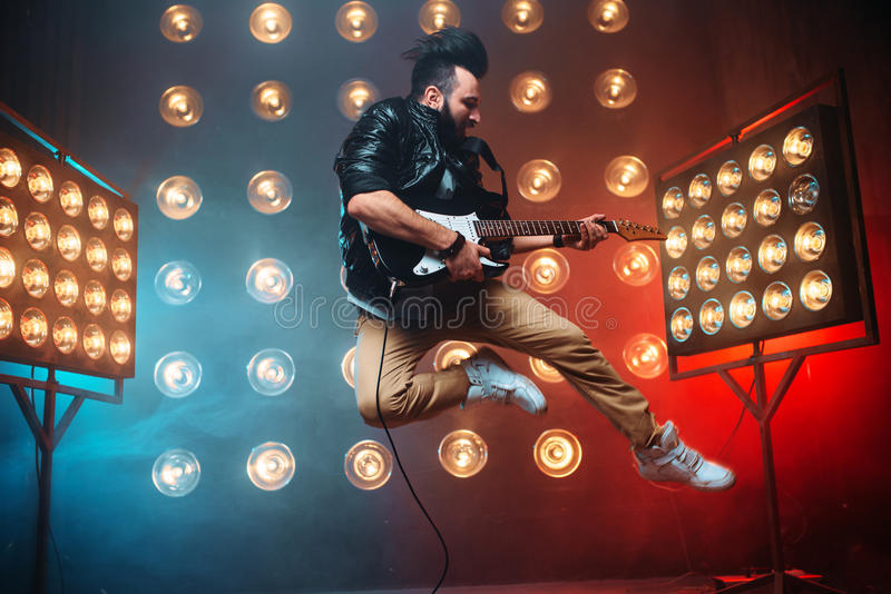 Male performer with electro guitar in a jump. On the stage with the decorations of lights. Music entertainment. Bearded musican song performing stock images