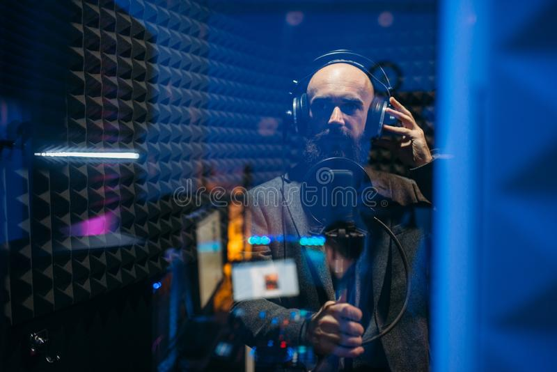 Male performer songs in audio recording studio. Male performer in headphones songs in audio recording studio. Musician  listens composition, professional music stock photography
