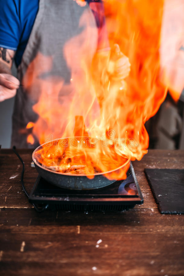Male person against frying pan with fire. Cooking sea bass fish fillet. Seafood preparation stock images