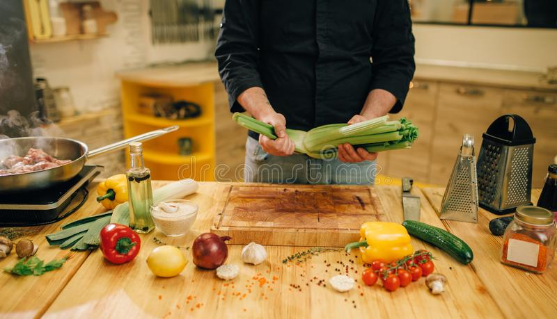 Male person cooking meat with vegetables in a pan royalty free stock images