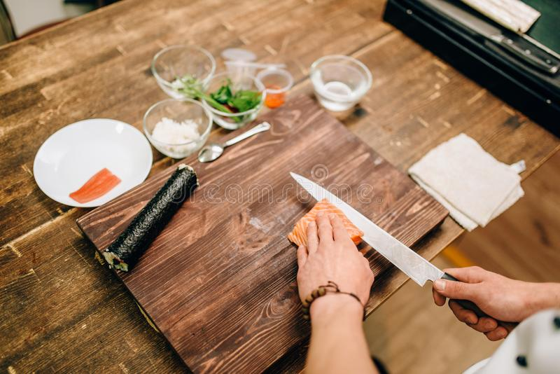 Male person cooking seafood, asian food. Male person cooking seafood on wooden table, asian food preparation process. Traditional japanese cuisine, sushi royalty free stock images