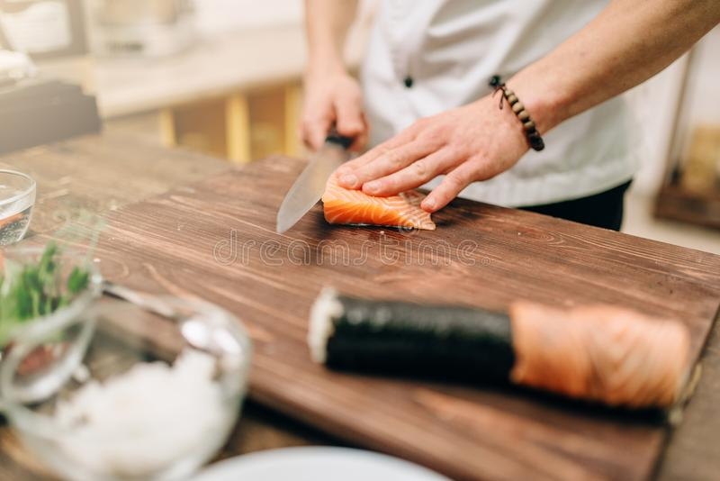 Male person cooking seafood, asian food. Male person cooking seafood on wooden table, asian food preparation process. Traditional japanese cuisine, sushi stock images