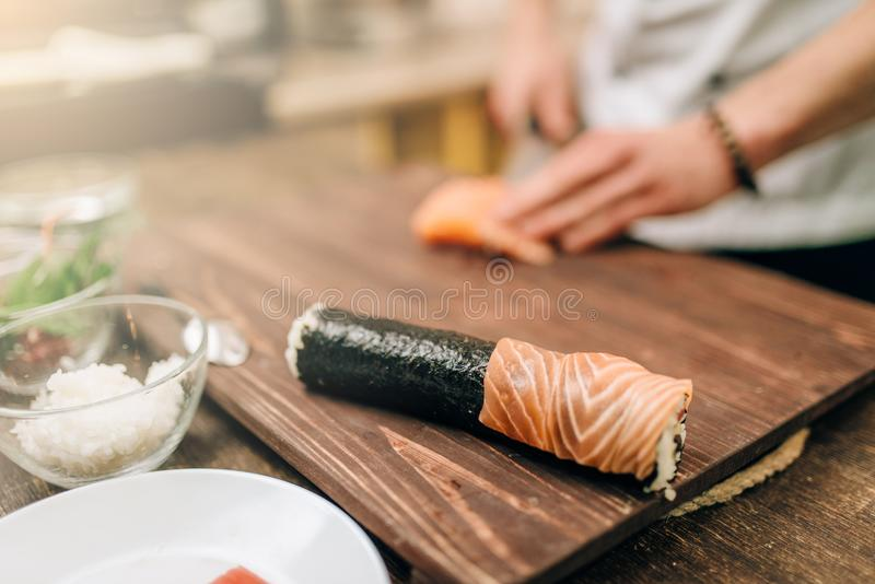 Male person cooking seafood, asian kitchen. Male person cooking seafood on wooden table, asian kitchen preparation process. Traditional japanese cuisine, sushi royalty free stock photo