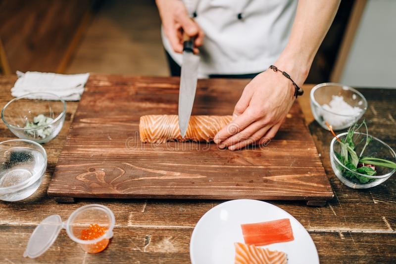 Male person cooking seafood, japanese food. Male person cooking seafood on wooden table, japanese food preparation process. Traditional asian cuisine, sushi stock images