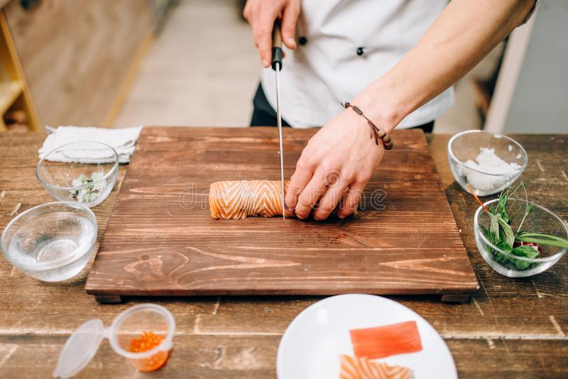 Male person cooking seafood, japanese food. Male person cooking seafood on wooden table, japanese food preparation process. Traditional asian cuisine, sushi royalty free stock images