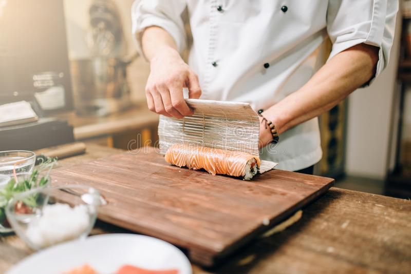 Male person cooking seafood, japanese kitchen. Male person cooking seafood on wooden table, japanese kitchen preparation process. Traditional asian cuisine royalty free stock photography