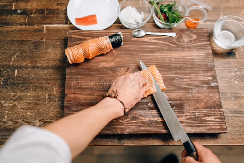 Male person cooking seafood, asian kitchen. Male person cooking seafood on wooden table, asian kitchen preparation process. Traditional japanese cuisine, sushi stock photo