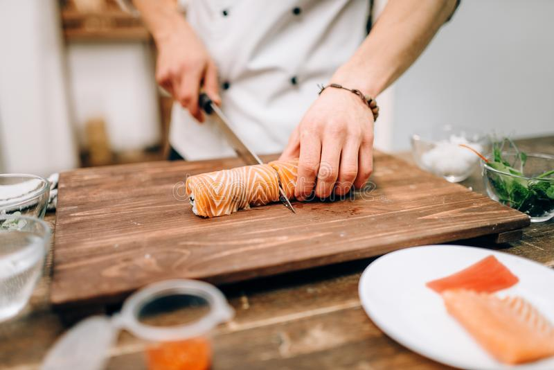 Male person cooking sushi, japanese food. Male person cooking sushi on wooden table, japanese food preparation process. Traditional asian cuisine, seafood stock photos