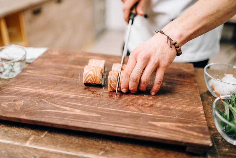 Male person cooking sushi, japanese food. Male person cooking sushi on wooden table, japanese food preparation process. Traditional asian cuisine, seafood royalty free stock image