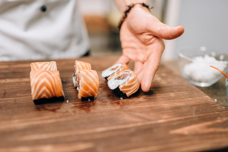 Male person cooking sushi, japanese kitchen. Male person cooking sushi on wooden table, japanese kitchen preparation process. Traditional asian cuisine, seafood stock photography