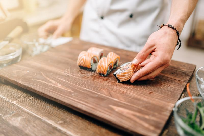 Male person cooking sushi, japanese kitchen. Male person cooking sushi on wooden table, japanese kitchen preparation process. Traditional asian cuisine, seafood royalty free stock photography