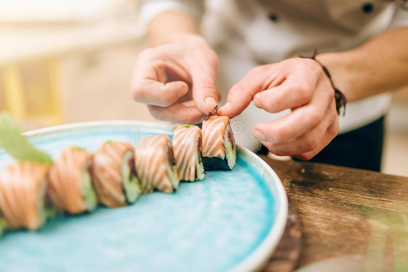 Male person cooking sushi rolls, japanese food. Male person cooking sushi rolls with salmon on wooden table, japanese food preparation process stock photo