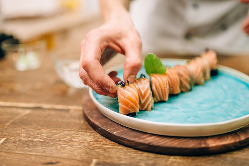 Male person cooking sushi rolls with salmon. On wooden table, japanese food preparation process. Traditional asian cuisine, seafood delicious stock images