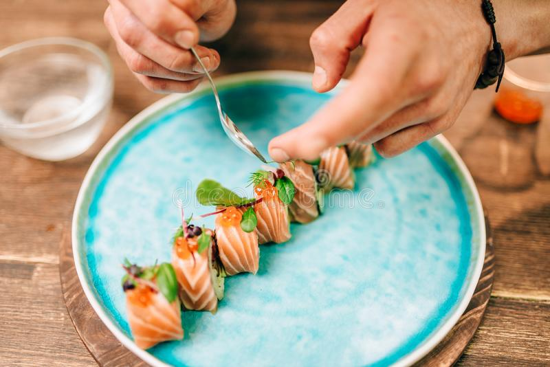 Male person cooking sushi rolls with salmon. On wooden table, japanese food preparation process. Traditional asian cuisine, seafood delicious stock photos