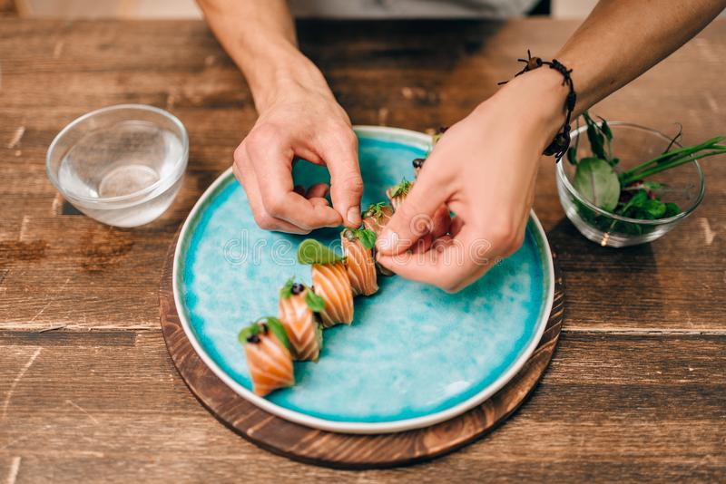 Male person cooking sushi rolls with salmon. On wooden table, japanese food preparation process. Traditional asian cuisine, seafood delicious royalty free stock photos