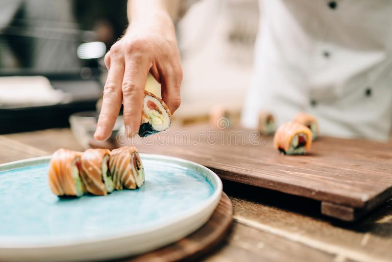 Male person cooking sushi rolls on wooden table. Japanese kitchen preparation process. Traditional asian cuisine, seafood delicious royalty free stock photography