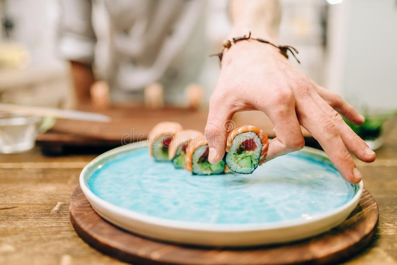 Male person cooking sushi rolls on wooden table. Japanese kitchen preparation process. Traditional asian cuisine, seafood delicious stock image
