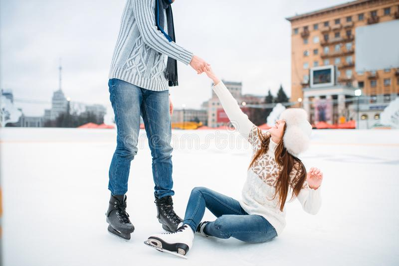 Male person helps a woman to get up, skating rink. Male person helps a women to get up, love couple on skating rink. Winter ice-skating on open air, active stock image