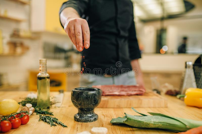 Male person marinating raw meat on wooden board royalty free stock photo