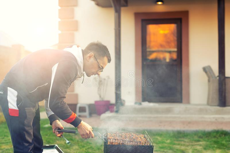 Male person preparing chicken wings on grill at open fire brazier. Barbecue  friens home party at house backyard. Weeken bbq royalty free stock photo