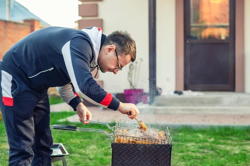 Male person preparing chicken wings on grill at open fire brazier. Barbecue  friens home party at house backyard. Weeken bbq royalty free stock images